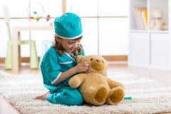 Doktor des kleinen Mädchens mit Teddybären lizenzfreie stockbilder