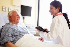 Doktor With Digital Tablet som talar till patienten i sjukhus Arkivbild