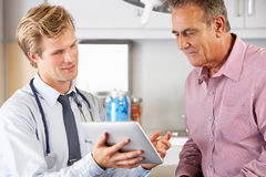 Doktor Discussing Records With Patient, der Digital-Tablette verwendet Stockbild