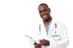 Doktor in einer Uniform, die ein Klemmbrett hält Lizenzfreie Stockfotografie