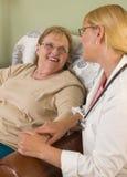 Doktor eller sjuksköterska Talking till att sitta den höga kvinnan Arkivbild