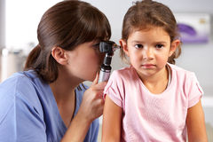 Doktor Examining Childs Ears In Büro Doktors Stockbild