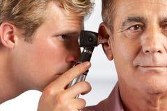 Doktor Examining Male Patients Ears Stockbilder