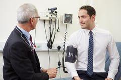 Doktor Examining Senior Patient i sjukhus royaltyfria bilder