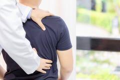 Doktor Examining Sore Back mischt vom junger Mann-Sitzen hemdlos und gestürzt vorbei auf Tabelle mit stockbild