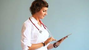 Doktor för ung kvinna som arbetar med en digital minnestavla stock video