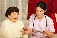 Doktor gibt der älteren Frau Pillen Stockfoto