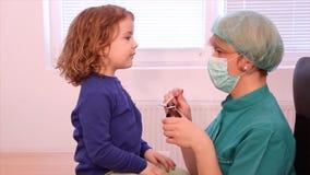 Doktor gibt einem kleinen Mädchen eine Heilung stock video