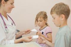 Doktor gibt Rezept für Bruder und Schwester Lizenzfreie Stockbilder