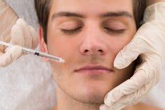 Doktor Giving Injection On stellen vom Mann gegenüber Stockbild