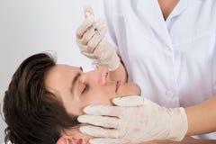 Doktor Giving Injection On stellen vom Mann gegenüber Lizenzfreie Stockfotografie
