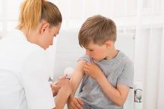 Doktor Giving An Injection till pojken royaltyfria bilder