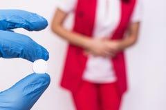 Doktor hält eine Pille in ihrer Hand vor dem hintergrund eines Mädchens, das Bauchschmerzen und Aufblähung hat, Medizin stockbild