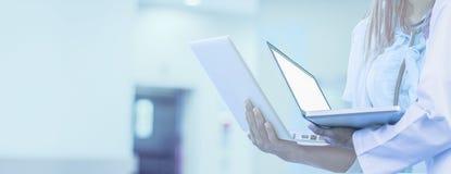 Doktor hält Laptop in der Hand, Hintergrund ist Krankenhaus, für horizontale panoramische Art der Netzfahne, medizinische Technol lizenzfreies stockfoto