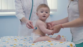 Doktor hören die Rückseite des Babys mit Stethoskop stock video footage