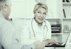 Doktor hört auf reifen Patienten Lizenzfreies Stockfoto