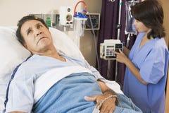 Doktor Helping Middle Aged Man Lizenzfreies Stockfoto