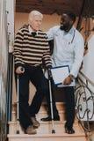 Doktor Helps Mann gehen unten Treppe Pflegeheim stockfotos