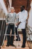 Doktor Helps Pensionär auf Go-Karten caregiver stockbilder