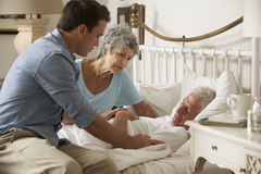 Doktor On Home Visit, das Gesundheit des älteren männlichen Patienten mit Frau bespricht Stockfotos