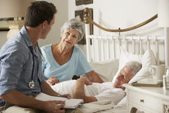 Doktor On Home Visit, das Gesundheit des älteren männlichen Patienten mit Frau bespricht Stockbild
