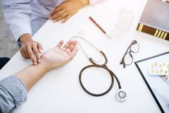 Doktor i det vita laget som tar och kontrollerar den tålmodiga handledpaien för ` s Royaltyfria Bilder