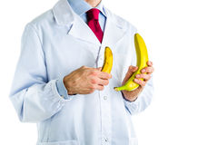 Doktor i det vita laget som visar stora och små bananer Royaltyfri Foto