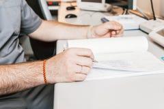 Doktor i ett ämbetsdräktsammanträde på en tabell i ett sjukhuskontor Royaltyfri Fotografi