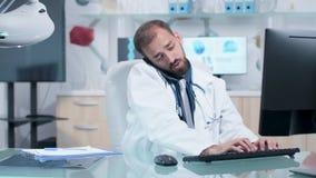 Doktor i hans moderna kontor som talar på telefonen lager videofilmer