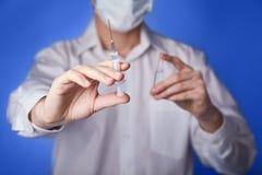 Doktor i maskering med en injektioninjektionsspruta på den blåa bakgrunden royaltyfri fotografi