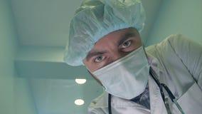 Doktor i maskeringen som ner ser på patienten som kontrollerar hans medvetenhet lager videofilmer