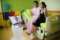 Doktor i sjukhussamtal med patienten på tålmodigt rum vid robo Arkivbild