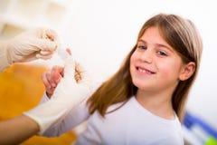 Doktor in ihrer Praxis, die einen Verband auf einige Schmerzen eines kleinen Mädchens setzt Lizenzfreies Stockfoto