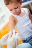 Doktor in ihrer Praxis, die einen Verband eines Kindes des kleinen Jungen setzt Stockfotos