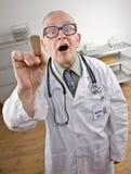 Doktor im Labormantel unter Verwendung des Zungesenkers Stockfotografie