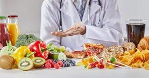 Doktor im Mantel, der gute und schlechte Nahrung vergleicht stockbild
