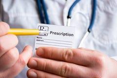 Doktor im Vordergrund, der Probe der Verordnung oder des Rezepts für Droge, andere Hand hält, zeigt Bezeichnung von Verordnung me stockfotos