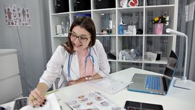 Doktor im weißen Laborkittel, der am Arbeitsplatz sitzt und Dokumente liest stock video footage