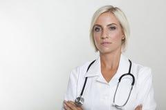 Doktor im weißen Mantel und im Stethoskop mit den Armen gekreuzt Stockbild