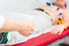 Doktor kontrolliert患者EKG在Arztpraxis 库存图片