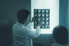 Doktor Looking am Röntgenstrahl-Film geduldige Frau, die auf Diagnose hört lizenzfreie stockbilder