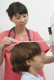Doktor Measuring Height Of en pojke Arkivbild