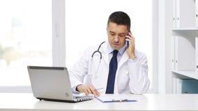 Doktor med bärbara datorn som kallar på smartphonen stock video