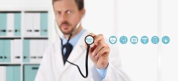 Doktor med en stetoskop i händerna och läkarundersökningsymbolerna royaltyfri bild