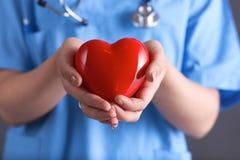 Doktor med hållande hjärta för stetoskop, på Fotografering för Bildbyråer