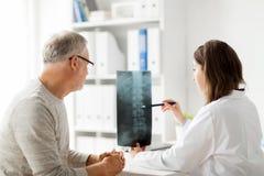 Doktor med inbindningsröntgenstrålen och hög man på sjukhuset Royaltyfri Fotografi