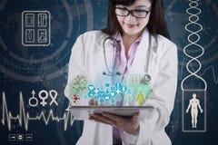 Doktor med medicinska apps på den digitala minnestavlan Arkivbild