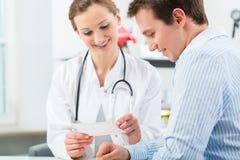 Doktor med patienten, i att konsultera för klinik Royaltyfri Foto