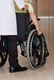 Doktor med patienten på hjulstol Fotografering för Bildbyråer