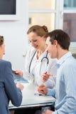 Doktor med patienter i konsultera i klinik Fotografering för Bildbyråer